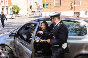 Traffic police officer checks documents of female driver on the streets of Rome
